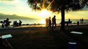 La gente siluetea cerca de la playa en puesta del sol almacen de metraje de vídeo