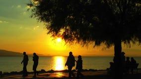 La gente siluetea cerca de la playa en puesta del sol almacen de video