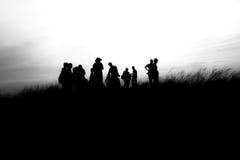 La gente siluetea encima de la montaña Fotografía de archivo libre de regalías