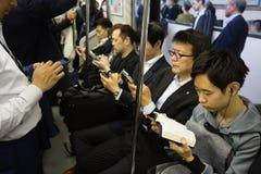 La gente in smartphones di uso del sottopassaggio e leggere i libri a Tokyo fotografie stock libere da diritti