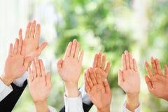La gente solleva le loro mani in su sopra priorità bassa verde Fotografia Stock Libera da Diritti