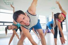 La gente sorridente che fa la forma fisica di potere si esercita alla classe di yoga Fotografie Stock Libere da Diritti