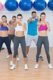 La gente sorridente che fa la forma fisica di potere si esercita alla classe di yoga Fotografia Stock