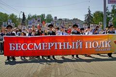 La gente sostiene la bandera del regimiento y de los retratos inmortales de sus parientes el día de la victoria en Stalingrad Fotografía de archivo libre de regalías