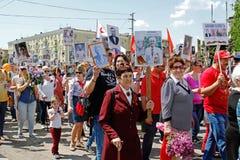 La gente sostiene los retratos de sus parientes en el ` inmortal del regimiento del ` de la acción el día de la victoria en Stali Imágenes de archivo libres de regalías
