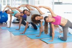 La gente sportiva che fa l'allungamento si esercita nello studio di forma fisica Immagini Stock Libere da Diritti