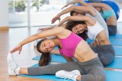 La gente sportiva che fa l'allungamento si esercita nello studio di forma fisica Immagine Stock Libera da Diritti
