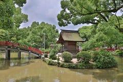 La gente sta attraversando il ponte rosso famoso del santuario di Dazaifu fotografia stock