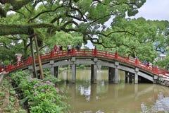 La gente sta attraversando il ponte rosso famoso del santuario di Dazaifu fotografia stock libera da diritti
