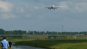 La gente sta guardando l'aeroplano avvicinarsi a all'aeroporto video d archivio