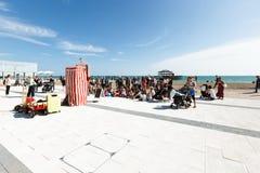 La gente sta guardando una prestazione di un teatro del burattino a Brighton, sedie di spiaggia Fotografie Stock Libere da Diritti