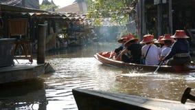 La gente sta nuotando in una barca su un fiume marrone in Tailandia nella foschia Gente di camminata lungo la riva e la guida sop stock footage