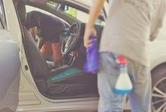 La gente sta pulendo le automobili, spruzzanti le automobili fuori e dentro immagini stock