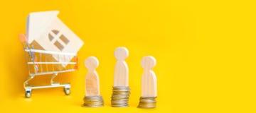 La gente sta sulle monete sui precedenti di una casa di legno in carrello del supermercato Concetto del bene immobile Acquisto, v Fotografia Stock Libera da Diritti