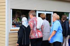 La gente sta in una coda al chiosco per la vendita delle verdure Fotografie Stock Libere da Diritti
