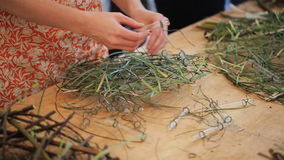 La gente sta vicino alla tavola di legno nello studio di arte e crea le corone da erba stock footage