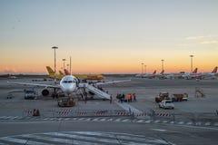 La gente sube a un aeroplano comercial en el aeropuerto de Milan Malpensa en la puesta del sol en Milán Imagen de archivo