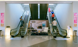 La gente sube y desciende en la escalera móvil en el centro comercial Auchan Fotografía de archivo libre de regalías