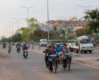 La gente sui ciclomotori guida su una via della citt? Traffico tipico in una citt? asiatica Vita di citt? immagine stock