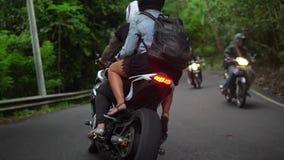 La gente sui motocicli guida sulla strada rurale in tropici, giovani coppie ha viaggio stock footage