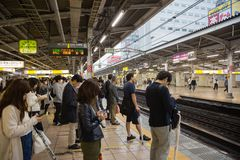 La gente sul binario che aspetta il treno di JUNIOR a Tokyo immagini stock