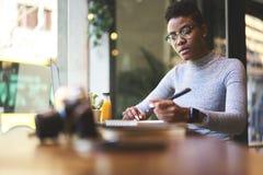 La gente sul lavoro che fa lavoro a distanza in caffetteria con il collegamento libero di wifi Fotografia Stock Libera da Diritti