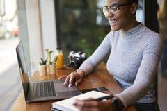 La gente sul lavoro che fa lavoro a distanza in caffetteria facendo uso di Internet senza fili libero Immagine Stock