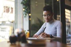 La gente sul lavoro che pubblica sulla pagina Web della versione online dell'edizione che si siede in caffè moderno Fotografia Stock Libera da Diritti