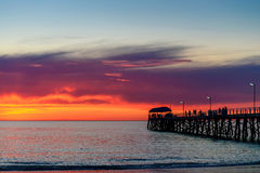 La gente sul pilastro al tramonto Fotografia Stock