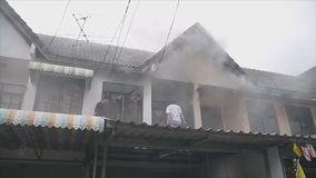 La gente sul tetto contribuisce ad estinguere un fuoco quella casa bruciante i archivi video