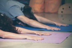 La gente sulla classe di yoga dell'interno immagini stock