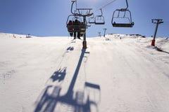 La gente sulla seggiovia dello sci nelle alpi soleggiate di inverno in Austria Immagine Stock