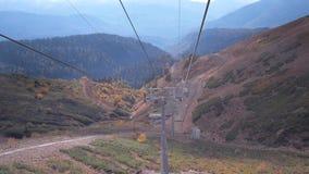 La gente sulla seggiovia e sul bello paesaggio della montagna stock footage