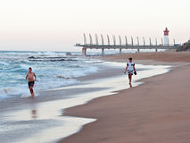 La gente sulla spiaggia alle rocce di Umhlanga, con il pilastro di millennio ed il faro nei precedenti Immagini Stock