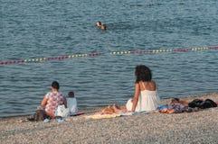 La gente sulla spiaggia con l'uomo peloso Fotografia Stock Libera da Diritti