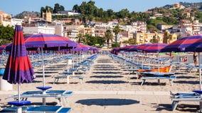 La gente sulla spiaggia della città di Giardini Naxos nella mattina Immagine Stock