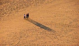 La gente sulla spiaggia sabbiosa capa della vite senza fine al tramonto Immagini Stock