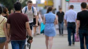 La gente sulla via del passaggio pedonale Pedoni in via moderna della città La gente attraversa l'intersezione indietro osserva immagine stock