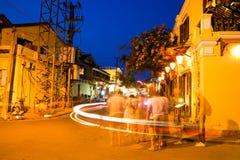 La gente sulla via della città antica con effetto lungo di esposizione, sito di Hoi An del patrimonio mondiale dell'Unesco fotografie stock