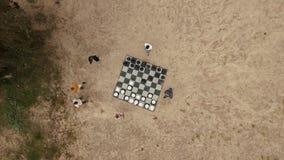La gente superior del tiro de la antena que juega a ajedrez gigante figura el juego en la playa de la arena cerca de árbol metrajes