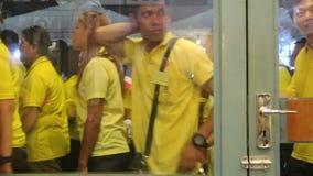 La gente tailandesa lleva las camisas amarillas está caminando detrás a casa después de que para ver a su rey Rama 10 de la majes almacen de metraje de vídeo