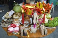 La gente tailandesa prepara la comida de ofrecimiento sacrificatoria en la tabla para ruega Foto de archivo