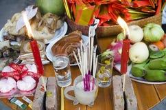 La gente tailandesa prepara la comida de ofrecimiento sacrificatoria en la tabla para ruega Imagenes de archivo