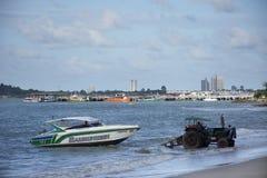 La gente tailandesa que conduce el tractor va al mar para guardar y levantar el barco de la velocidad para ir a almacenar en Rayo imagen de archivo libre de regalías