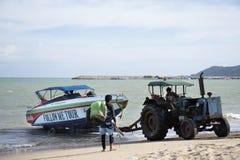 La gente tailandesa que conduce el tractor va al mar para mantener y levantarse el barco de la velocidad para ir a almacenar en l foto de archivo libre de regalías