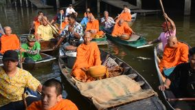 La gente tailandesa ruega y pone la comida y ofrendas de la cosa a la procesión de los monjes en barco