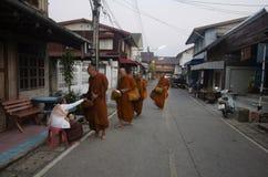 La gente tailandese ha messo le offerti dell'alimento alla passeggiata della processione dei monaci sulla strada Fotografia Stock