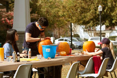 La gente talla y pinta las calabazas de Halloween Imágenes de archivo libres de regalías