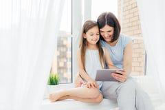 La gente, tecnologia, famiglia, concetto dei bambini Giovane altra e sua piccola figlia positiva si siede sul davanzale della fin immagine stock libera da diritti