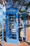 La gente tedesca dell'uomo anziano che per mezzo del telefono pubblico dice alla famiglia a Fotografia Stock
